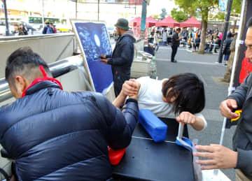 腕相撲の体験コーナーもお目見えした「カワサキよりみちサーカス」=JR川崎駅東口