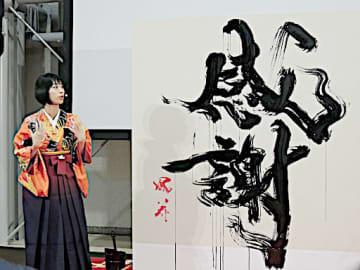 「感謝」と書き上げ、漢字の成り立ちを説明する涼風花さん=16日、大阪市北区の阪急三番街