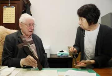 ルーメル神父の遺品でもある十字架を、東京都千代田区のSJハウスで手にして語り合うモール神父(左)と江島さん(撮影・浜岡学)