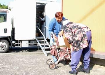 トラックを降り、客の手押し車まで荷物を運ぶ成松さん(左)=五島市玉之浦町