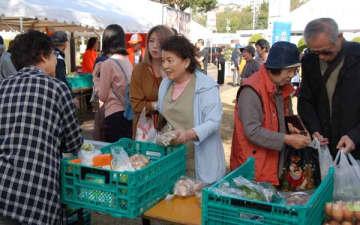 【地元産の野菜を買い求める市民ら=亀山市東御幸町の市文化会館で】