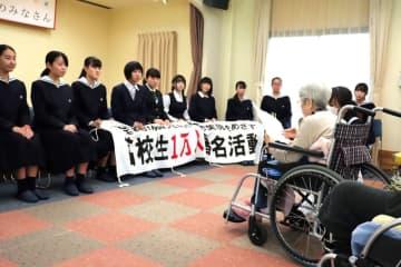 大田さん(右)の話を聞く高校生平和大使ら=西海市西彼町、原爆被爆者特別養護ホームかめだけ