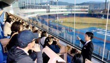 菊池さん(右)の解説を聞きながらレース観戦する参加者