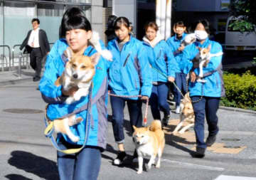 避難訓練で、犬を抱きかかえて公園へと急ぐ学生