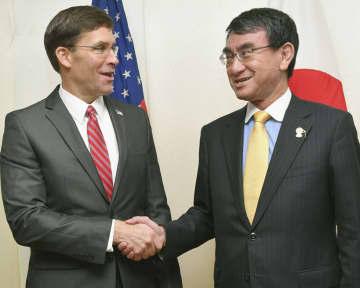 会談後に握手するエスパー米国防長官(左)と河野防衛相=18日、バンコク(共同)