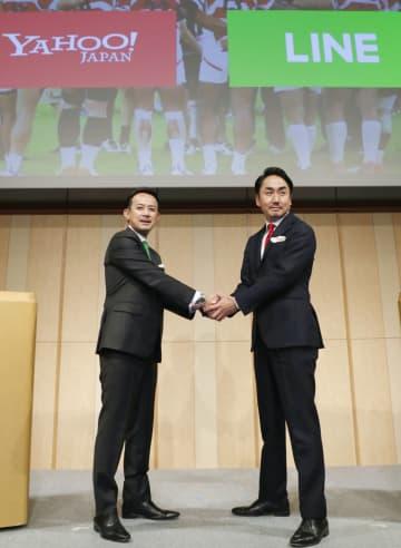 経営統合で合意し、記者会見で握手するヤフーの親会社ZHDの川辺健太郎社長(左)とLINEの出沢剛社長=18日午後、東京都港区