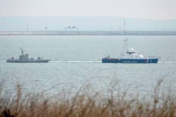 17日、ウクライナ南部クリミア半島沖でロシア国境警備局の警備艇(右)に伴われて返還場所に向かうウクライナ海軍の艦船(タス=共同)