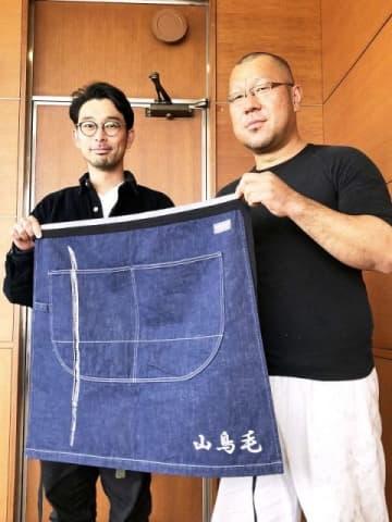 山鳥毛の刀身とロゴ入り前掛けを手にする安藤さん(右)と越智課長