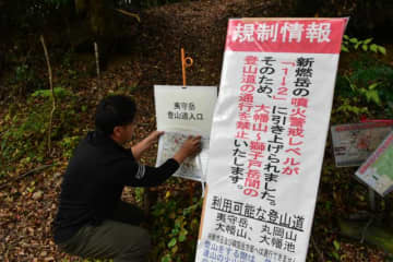 登山道入り口に通行規制情報を掲示する小林市職員=18日午前、小林市南西方