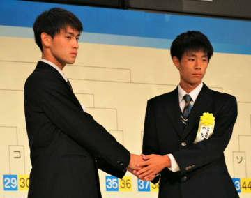 1回戦で対戦する矢板中央の主将と握手する大分の永松副主将(右)=18日、東京都