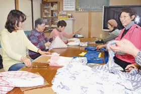 和やかな雰囲気の中、清拭布作りに取り組む崎守町町会メンバー