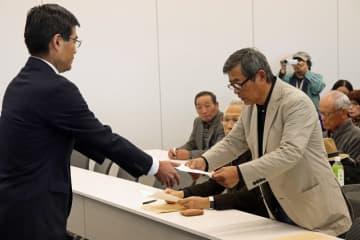 平田副知事(左)に宣言文を手渡す岩下さん=県庁