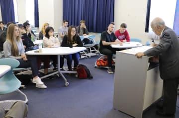 築城さん(右)が英語で話す被爆体験に聞き入る留学生ら=長崎外国語大