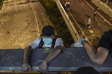 A protester lowers himself down from a bridge to a highway, to escape from Hong Kong Polytechnic University campus and from police, in Hung Hom district in Hong Kong on November 18, 2019. Photo: Ye Aung Thu/AFP.