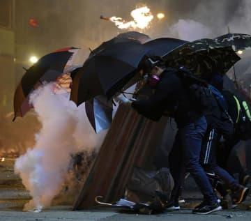 香港理工大周辺で、警官隊が放った催涙ガスの白煙が上がるなか、前進するデモ隊=18日夜、香港(共同)