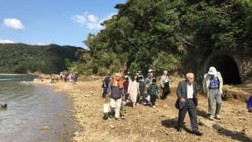 文学作品の舞台となった海辺を歩く参加者。右奥は震洋艇の格納壕跡=瀬戸内町の加計呂麻島