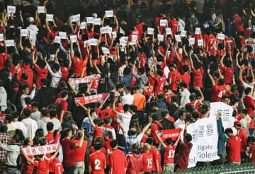 サッカーW杯アジア2次予選の香港―カンボジア戦で、中国国歌の演奏中にフィールドに背中を向けてブーイングを浴びせる香港サポーター=19日、香港(共同)