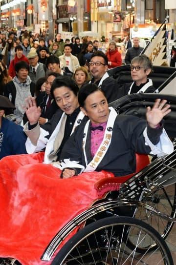 新京極通を人力車に乗って「お練り」をする岡村隆史さん(右)と堤真一さん=19日午後6時9分、京都市中京区