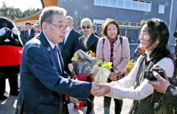 町職員らに見送られる中、町民と握手を交わす渡辺町長(左)