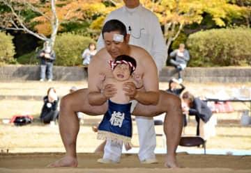 選手に抱えられての稚児土俵入りで、思わず泣き出す子ども=有田町の白磁ケ丘相撲場