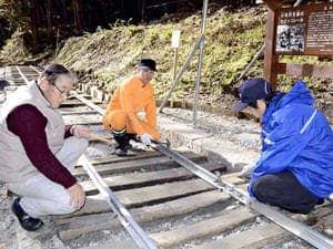 森林鉄道を復元した武田さん(左)ら作業参加者。モニュメントを観光復興に活用したい考え