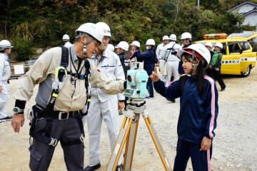 測量機器の説明を聞く弓削小児童(右)