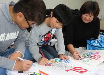 滋賀県をテーマにしたヘッドマークを描く親子(滋賀県長浜市港町・湖北勤労者福祉会館「臨湖」)