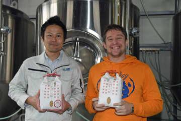 ビールのタンクを背に「スマート米」の袋を手にするバーンズさん(右)と赤石さん