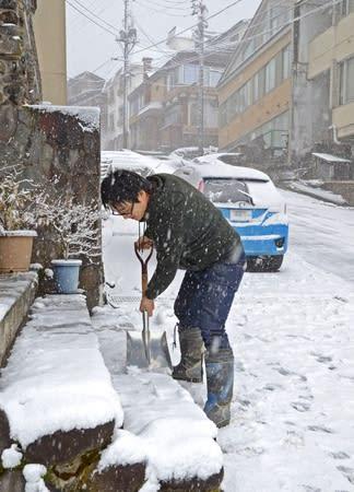 まとまった雪が降り、燕温泉の旅館前で雪かきをする経営者=20日、妙高市