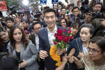 20日、タイ・バンコクで憲法裁判所に到着し、支持者に囲まれる「新未来党」のタナトーン党首(中央)(AP=共同)