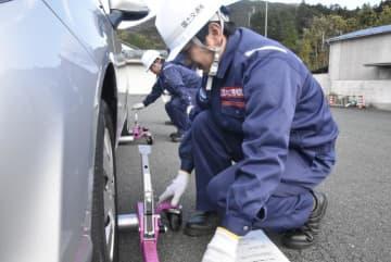 車両のタイヤに簡易移動器具を装着する国土交通省大洲河川国道事務所職員=20日午後、大洲市北只