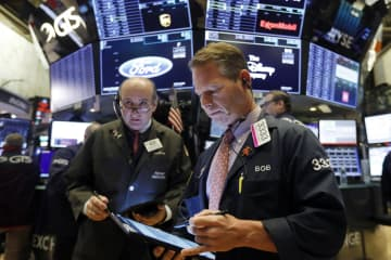 ニューヨーク証券取引所のトレーダーたち=20日(AP=共同)