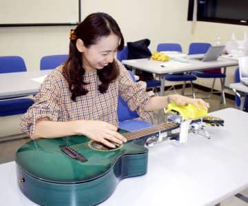 開発を手掛けた補助装置を付け、ギターを演奏する西ノ平志子さん=8月、佐賀市