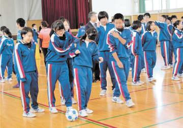 アイマスクをしてブラインドサッカーを体験する生徒ら