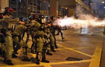 デモ隊に向かって催涙弾を発砲する警官隊=20日、香港・九竜地区