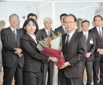 出迎えた職員から花束を受け取る吉田町長(右)=20日、大熊町役場