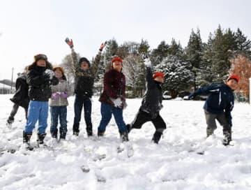 一面真っ白に染まった校庭で雪遊びを楽しむ寺田小の児童=20日朝、八幡平市西根寺田
