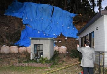 椎名公民館と子どもルーム(右)裏の崖で土砂崩れが発生した=20日午後、千葉市緑区富岡町