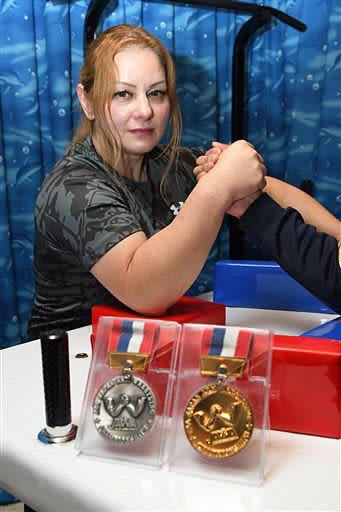 全日本選手権で獲得した金メダルと銀メダルを前にポーズをとる新岡さん