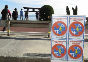 横断しないよう3カ国語で呼び掛ける国道161号沿いに設置された看板。琵琶湖上の大鳥居を見ようと、国道を横断する人が少なくない=高島市鵜川・白鬚神社前
