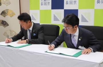 協定書にサインする波夛野社長(左)と中小路市町=長岡京市役所
