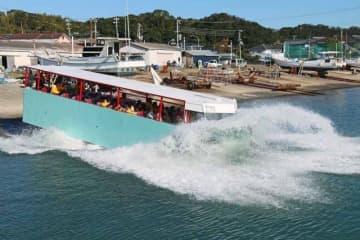 水しぶきを上げながら海に入る水陸両用観光バス(20日、和歌山県田辺市磯間で)