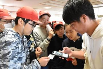 「KOTON」カードの実証実験に参加し、QRコードをスマホで読み取ってもらう児童ら