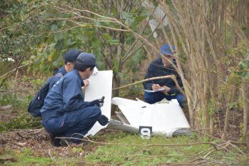 墜落した超軽量飛行機の翼の破片を調べる国交省の航空事故調査官ら=10月21日、かすみがうら市新治