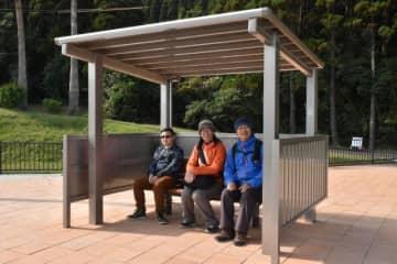 新設された待合所で、バスの到着を待つ外国人観光客