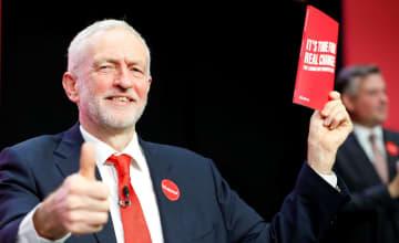 21日、英中部バーミンガムでマニフェストを手に取る労働党のコービン党首(ロイター=共同)