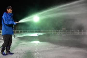 今季の営業開始を前に、リンクの結氷作業を進めるえびの高原荘の職員=21日午後、えびの市のえびの高原屋外アイススケート場