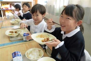ピーマンとサツマイモ、柿を使った給食を味わう向山小の子どもたち=熊本市中央区