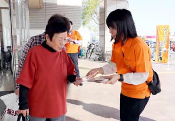 児童虐待防止の啓発チラシを受け取る買い物客=佐賀市のゆめタウン佐賀