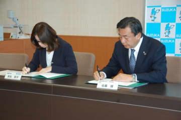 【協定書に署名する佐藤所長(右)と末松市長=鈴鹿市役所で】